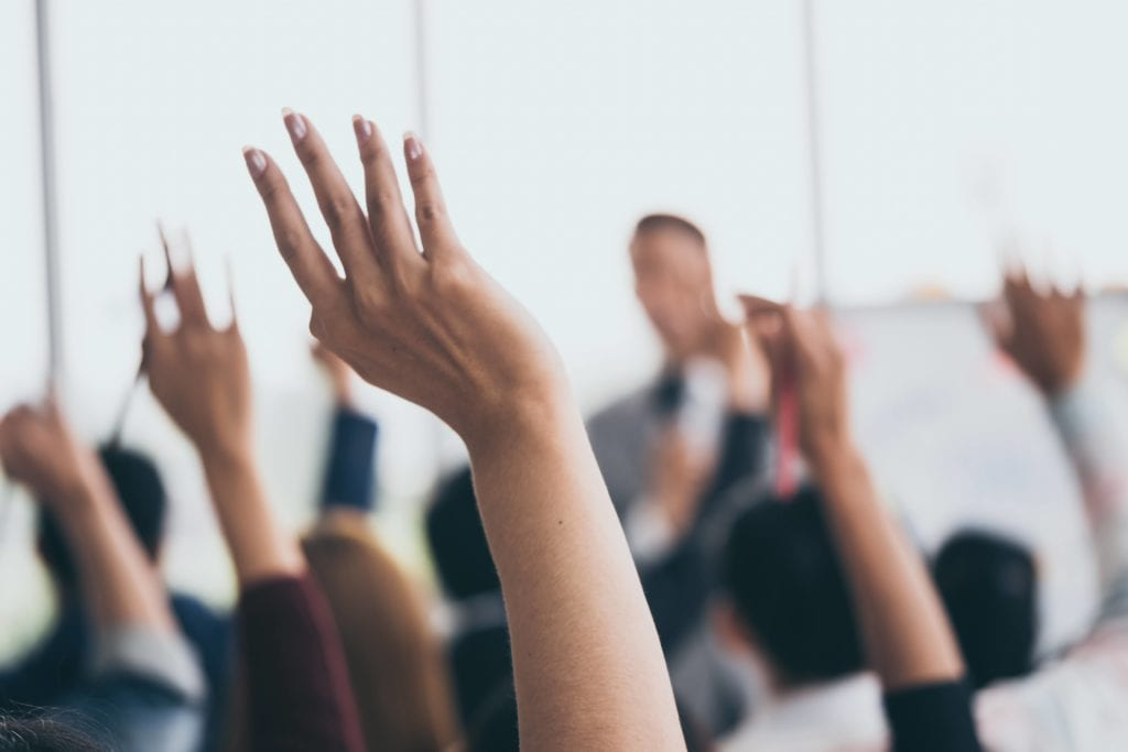 Audience raising hands at a business meeting