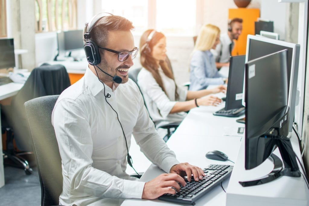 Happy male employee at computer with headset